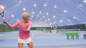 Young beautiful woman play tennis in slowmotion. Young beautiful woman is playing tennis at the indoors court. The woman professionally hits the tennis balls and stock video