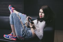 Young beautiful woman playing a console game on the couch  fashi Stock Photos