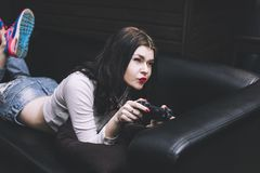 Young beautiful woman playing a console game on the couch  fashi. Young beautiful woman playing a console game on the couch sexy and fashionable Royalty Free Stock Photo