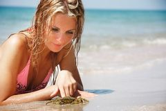 Young beautiful woman playing with crab Royalty Free Stock Photo