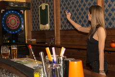 Young beautiful woman playing darts in a club.  royalty free stock photos