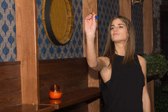 Young beautiful woman playing darts in a club stock image