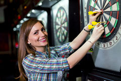 Young beautiful woman playing darts in a club Stock Photography
