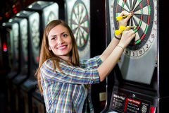 Young beautiful woman playing darts in a club Royalty Free Stock Photo