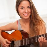 Young beautiful woman playing guitar Royalty Free Stock Photo