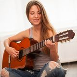 Young beautiful woman playing guitar Royalty Free Stock Photography