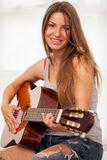 Young beautiful woman playing guitar Stock Images
