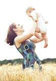 Young and beautiful woman playing with her infant baby in a mead Stock Image