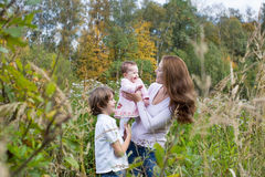 Young beautiful woman playing with her son and daughter in a colorful field Stock Photography