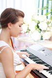 Young beautiful woman playing on piano Stock Image