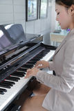 Young beautiful woman playing on piano Stock Photography