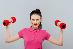 Young beautiful woman playing with two dumbbells on grey background royalty free stock images