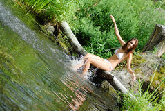 Young beautiful woman playing in wild river Royalty Free Stock Photography
