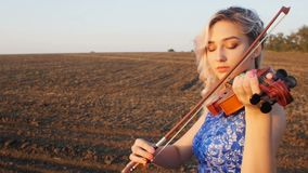 Young beautiful woman plays the violin in nature, the girl inspired moving bow along the strings of a musical instrument at sunset. In the field, concept hobby stock video
