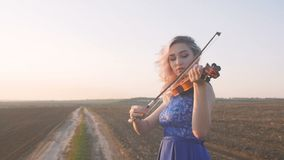 Young beautiful woman plays the violin in nature, the girl inspired moving bow along the strings of a musical instrument at sunset stock footage