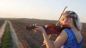 Young beautiful woman plays the violin in nature, the girl inspired moving bow along the strings of a musical instrument at sunset. In the field, concept hobby stock video footage