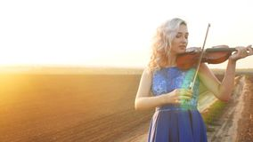 Young beautiful woman plays the violin in nature, the girl inspired moving bow along the strings of a musical instrument at sunset. In the field, concept hobby stock footage