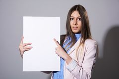 Young beautiful woman pointing at a blank sheet. For advertisement on a gray background Stock Photography