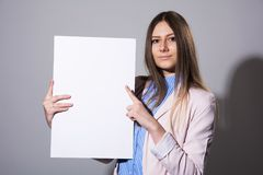Young beautiful woman pointing at a blank sheet. For advertisement on a gray background Stock Images