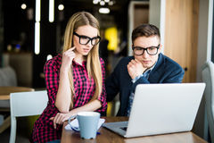 Young beautiful woman pointing at laptop with smile and discussing something with her coworker while standing at office Stock Photography