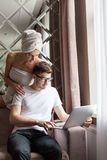 Young beautiful woman pointing at laptop with smile and discussing something with herman while standing near him. Woman Royalty Free Stock Photography