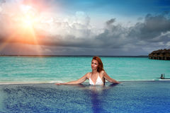 The young beautiful woman in the pool before the sea at sunset Stock Photos