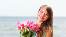 Young beautiful woman portrait on the beachflower  tulips Royalty Free Stock Image