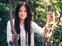 Young beautiful woman poses in green thickets Stock Photography