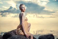 Young beautiful woman posing on the beach at sunset Stock Images