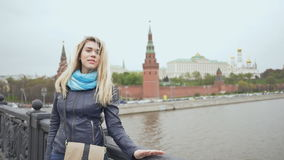 Young beautiful woman posing on the bridge on the background Red Square, Moscow Kremlin, Russia stock video