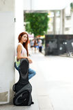 Young beautiful woman posing outdoor with her guitar gig bag Royalty Free Stock Photos