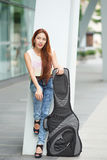 Young beautiful woman posing outdoor with her guitar gig bag Royalty Free Stock Photography