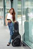 Young beautiful woman posing outdoor with her guitar gig bag Royalty Free Stock Photo