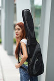Young beautiful woman posing outdoor with her guitar gig bag Stock Photography