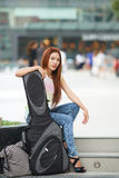 Young beautiful woman posing outdoor with her guitar gig bag Stock Images