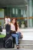 Young beautiful woman posing outdoor with her guitar gig bag Stock Photos