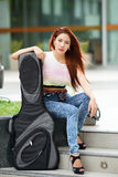 Young beautiful woman posing outdoor with her guitar gig bag Stock Photos