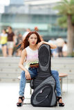 Young beautiful woman posing outdoor with her guitar gig bag Royalty Free Stock Images