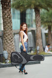 Young beautiful woman posing outdoor with her guitar gig bag Stock Photo