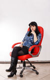 Young beautiful woman posing sitting on a red chair Royalty Free Stock Photography