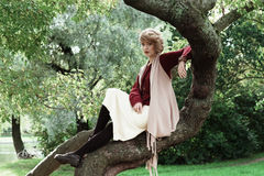 Young beautiful woman posing on a tree. Royalty Free Stock Photos