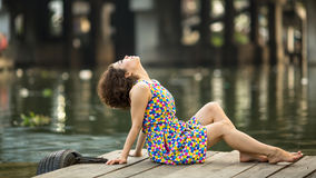 Young beautiful woman posing on a wooden river pier. Stock Image