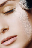 Young beautiful woman with a powder on the face Royalty Free Stock Image
