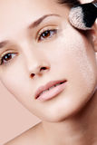 Young beautiful woman with a powder on the face Stock Photos