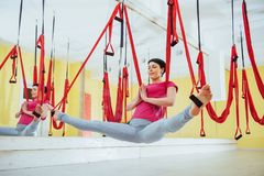 Young beautiful woman practicing yoga Fly with a hammock in the bright studio. The concept of mental and physical health Royalty Free Stock Photography