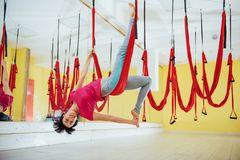 Young beautiful woman practicing yoga Fly with a hammock in the bright studio. The concept of mental and physical health Stock Photography