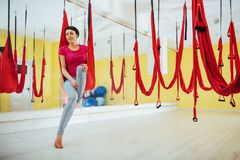 Young beautiful woman practicing yoga Fly with a hammock in the bright studio. The concept of mental and physical health Stock Image