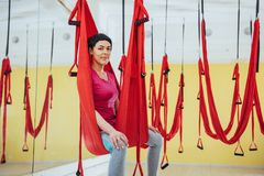 Young beautiful woman practicing yoga Fly with a hammock in the bright studio. The concept of mental and physical health Royalty Free Stock Images