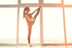 Young beautiful woman practicing yoga and gymnastic. Wellness concept. Classes in single sports. Stock Photos