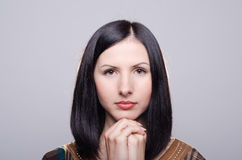 Young beautiful woman prays. On a grey background Royalty Free Stock Photo
